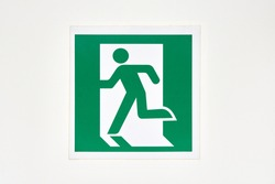 The sign of the direction to the evacuation exit on the wall in the shopping center is green