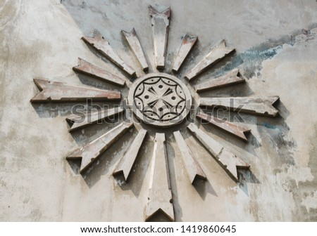 The sign of the sun is abstract on a gray concrete, cement wall.An ancient symbol
