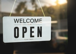 The signage welcomes we are open on a white acrylic sign hanging on the glass door in front of the restaurant. After closing because of Coronavirus and vintage solar situation, symbolic concepts.