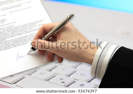 The Signature of Business Contract in front of Computer