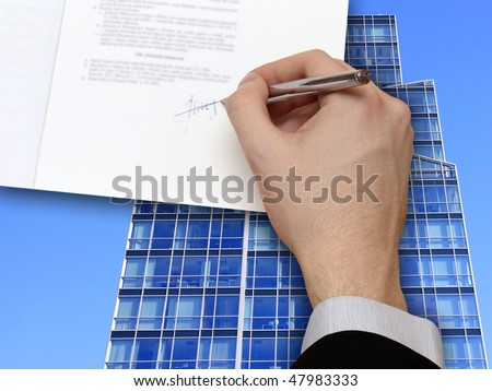 The Signature of Business Contract in front the Skyscraper on the blue Sky