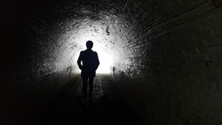 The silhouette behind the man went straight into the tunnel. The destination has light at the end.Black and white image means go to the goal.