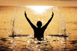The silhouette of a boy flicking the water with his arms in a