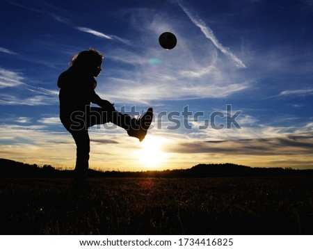 Photo of The silhouette of a boy kicking the ball while practicing football on an empty field at sunset, image of childhood, freedom and sport