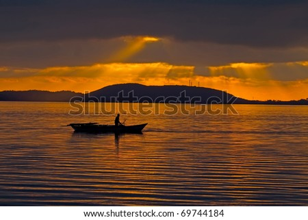 The silhouette of a fisherman with his boat in the lagoon of Amvrakikos during sunset