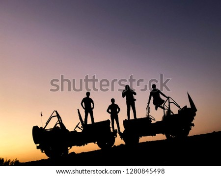 The silhouette of a group of people best friend having fun sitting and posing on a vehicle over sunset background. friendship concept. #1280845498