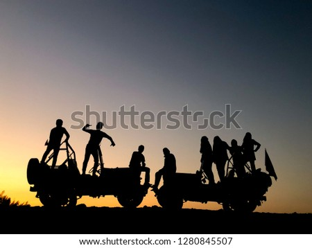 The silhouette of a group of people best friend having fun sitting and posing on a vehicle over sunset background. friendship concept. #1280845507