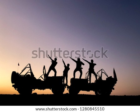 The silhouette of a group of people best friend having fun sitting and posing on a vehicle over sunset background. friendship concept. #1280845510