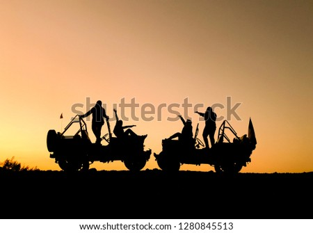 The silhouette of a group of people best friend having fun sitting and posing on a vehicle over sunset background. friendship concept. #1280845513