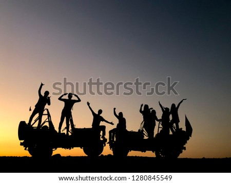The silhouette of a group of people best friend having fun sitting and posing on a vehicle over sunset background. friendship concept. #1280845549