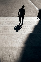 The silhouette of a guy with glasses, who rises up a concrete staircase to the top, creating an interesting reflection from his shadow. Contour sunlight. Art and street photography. Cool frame