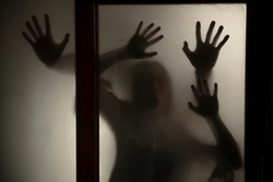 The silhouette of a human in front of a door at night.Scary scene Halloween concept of blurred silhouette,Ghost movies poster