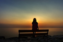 The silhouette of a lonely girl sitting on a bench on the top of the edge of a cliff and watching the sunset