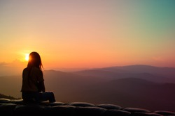 The silhouette of a lonely girl sitting on a bench watching the sunset on the top of the hill