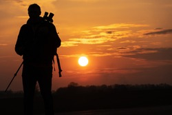 The silhouette of a man against the background of the sun and the beautiful sky. The outline of a man standing with a tripod and a camera in his hands against the background of the sunset.
