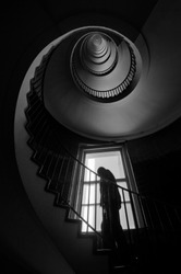 The silhouette of a man climbing the spiral staircase, dark black and white interior photography