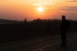 The silhouette of a person against the background of the sun and the beautiful sky. The outline of a man standing next to a tripod and a camera on the background of the sunset.