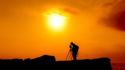 The silhouette of a photographer on a cliff captured during a mesmerizing sunset