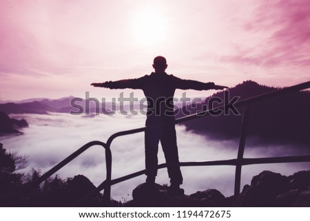 The silhouette of a single man with arms apart standing on top of a mountain against a surreal purple and red mountain landscape, concept of inspiration, enthusiasm and aspiration #1194472675