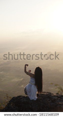 the silhouette of a traditional dancer above the peak in combination with the rising sun