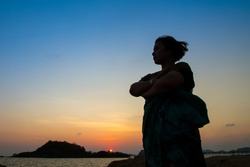 The silhouette of a woman in at twilight sunset on seashore, concept on the beach.