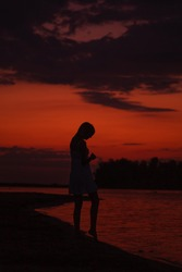 The silhouette of a woman in profile against the background of the sunset. A slender young woman walks along the river bank against the background of clouds and the beach.