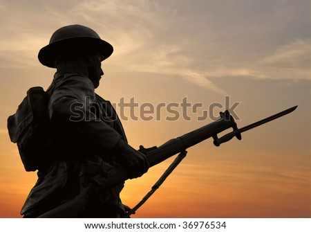 The silhouette of a WW1 soldier figure in a war monument against a ...