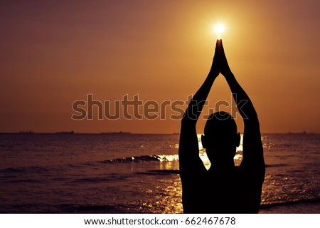 the silhouette of a young caucasian man practicing yoga in front of the sea in backlight