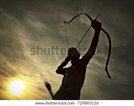 the silhouette of an archer with twilight background