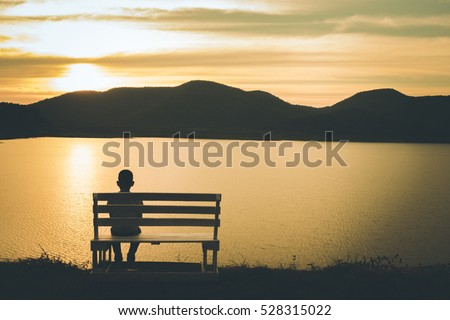 the silhouette of boy sitting...