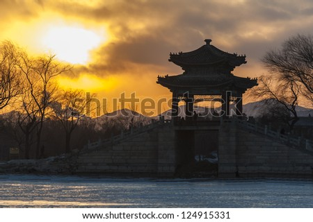 The silhouette of Chinese pavilion bridge against sunset