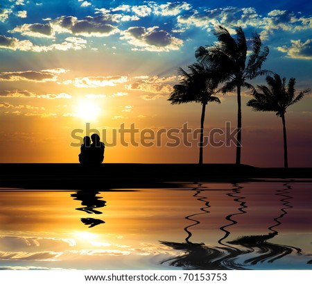 The silhouette of couple watching sunset on the beach - stock photo
