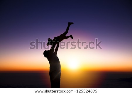 The silhouette of happy father and little girl with sunrise background