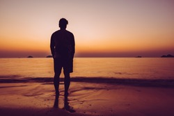 The silhouette of man sitting alone at the beach, concept of lonely, sad, alone, person space, alone and scared