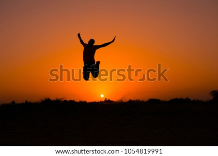 The silhouette of people jumping with sunset background,concept of happiness, joy, joyful life #1054819991
