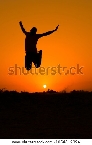 The silhouette of people jumping with sunset background,concept of happiness, joy, joyful life #1054819994