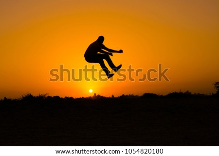 The silhouette of people jumping with sunset background,concept of happiness, joy, joyful life #1054820180
