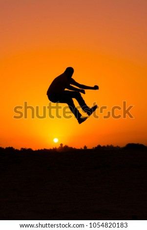 The silhouette of people jumping with sunset background,concept of happiness, joy, joyful life #1054820183