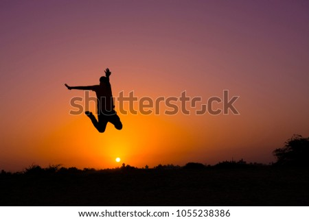 The silhouette of people jumping with sunset background,concept of happiness, joy, joyful life #1055238386