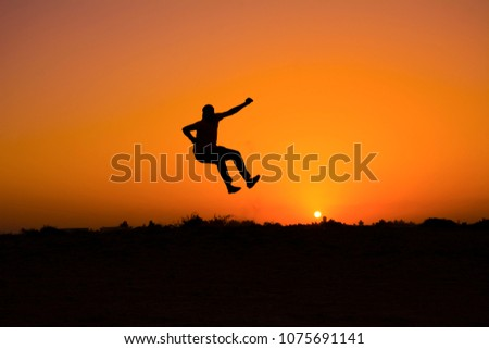 The silhouette of people jumping with sunset background,concept of happiness, joy, joyful life #1075691141