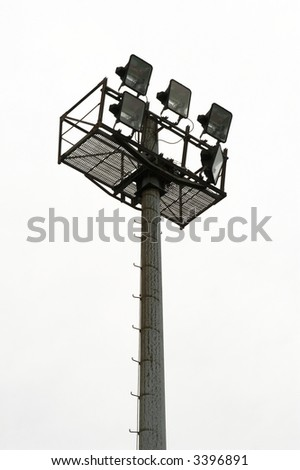 The silhouette of stadium light stand set against a grey sky