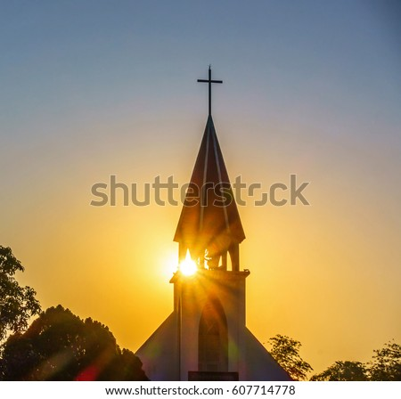 The silhouette of the cross and church bell tower in sunrise #607714778