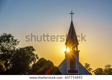 The silhouette of the cross and church bell tower in sunrise #607714895