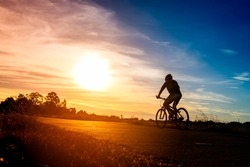The silhouette of the cyclist on road bike at sunset.A man ride on bike on the road. Sport and active life concept sunset time. A man riding on  bicycle in a park.