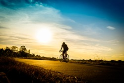 The silhouette of the cyclist on road bike at sunset. The cyclist in motion on the background of beautiful sunset.