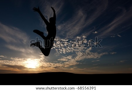The silhouette of the guy against a decline, the beautiful sky, jumps upwards