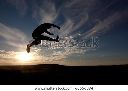 The silhouette of the guy against a decline, the beautiful sky, jumps upwards, a kick