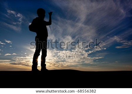 The silhouette of the guy against a decline, the beautiful sky, looks where that afar, holding a hand before eyes