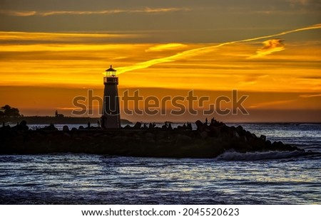 The silhouette of the lighthouse at sunset. Lighthouse at sunset sea. Sea sunset lighthouse. Sunset lighthouse