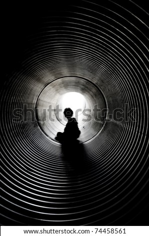 The silhouette of the sitting boy with light at the end of tunnel